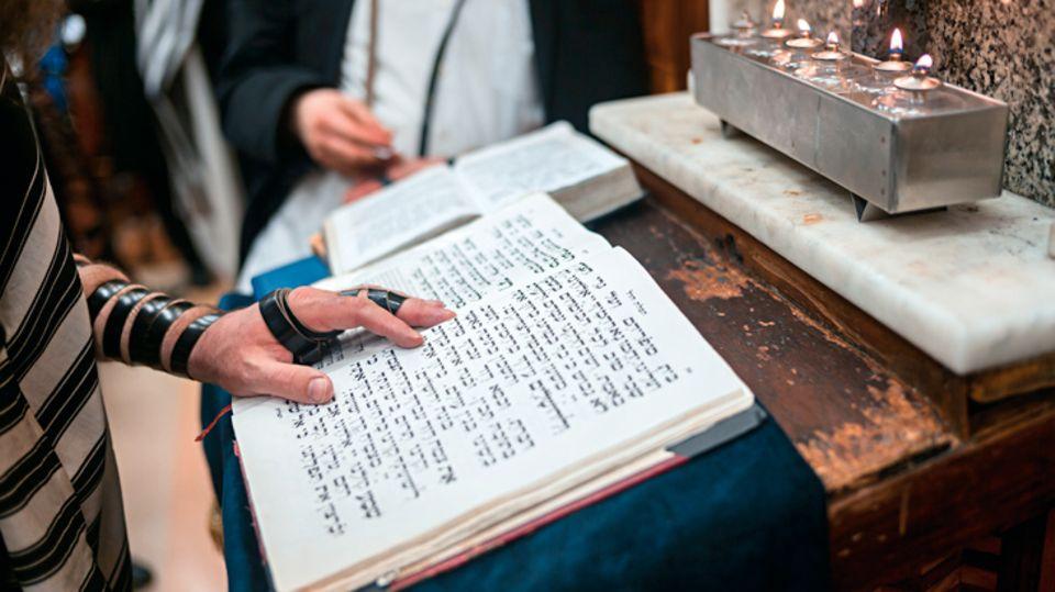 """Ein Blick in das aufgeschlagene Gebetbuch. Der Lederriemen """"Tefillin"""" wird dabei um Arm und Hand getragen"""