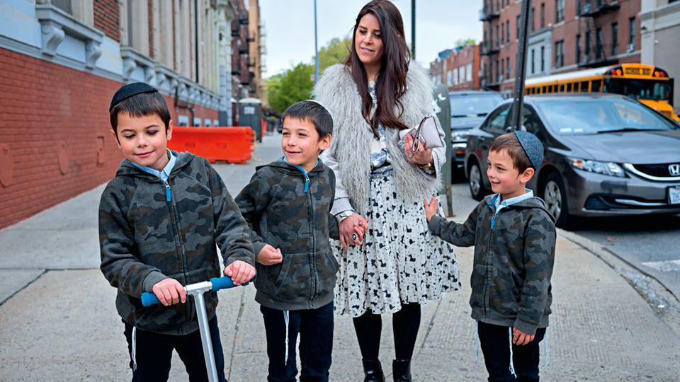 Devorah Bukiet mit dreien ihrer vier Söhne in Brooklyns Viertel Crown Heights. Die Frauen der Chabad kleiden sich modern. Aber auch sie tragen, wie alle anderen Chassidim-Frauen, Perücken. In den Bussen der Gemeinde sitzen die Menschen nach Geschlecht getrennt
