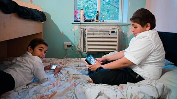 Zwei Jungs vertreiben sich während der Hochzeitsfeier von Bassy Schmukler und Chaim Landa die Zeit mit elektronischen Geräten. Bei Chabad sind sie erlaubt, in der Glaubensgemeinschaft Satmar dagegen verpönt