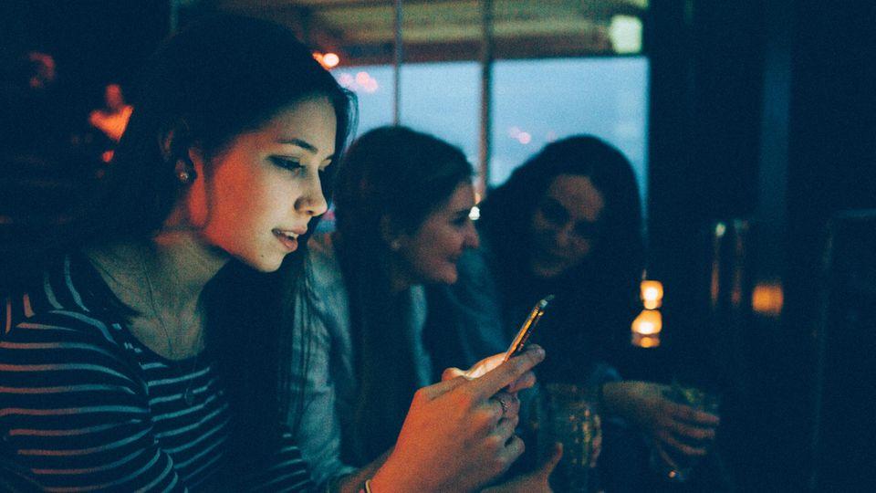 Eine Frau sitzt in einer Bar und hängt am Handy