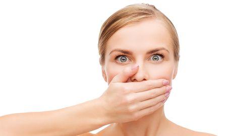 Eine junge Frau hält sich die Hand vor den Mund
