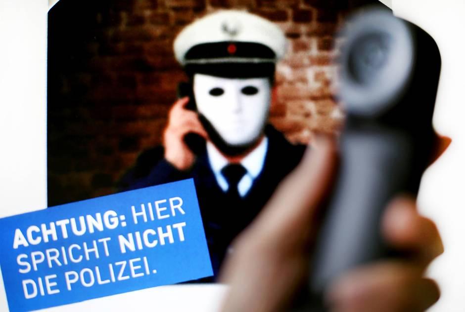 """Ein Telefonhörer vor einem Plakat der Polizei NRW mit der Aufschrift """"Achtung: Hier spricht nicht die Polizei"""""""