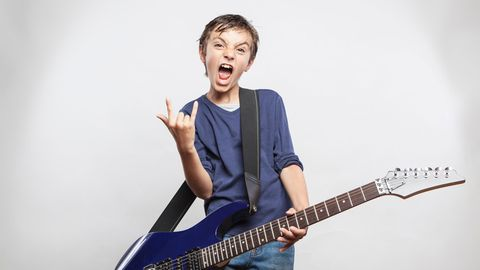 Ein Kind macht das Rockzeichen.