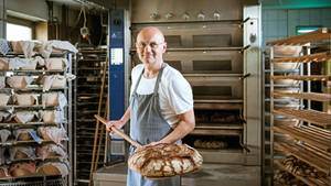 Bäcker Arnd Erbel steht in seiner Backstube und zeigt ein Brot, dass er gerade aus dem Ofen gezogen hat