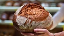 Ein Bäcker hält in seiner linken Hand ein Brot, im Hintergrund ist unscharf ein Regal mit Brotlaiben zu erkennen