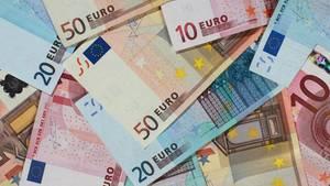 Gestapelte Euro-Scheine - Deutsche schauen zufrieden aufs Bankkonto