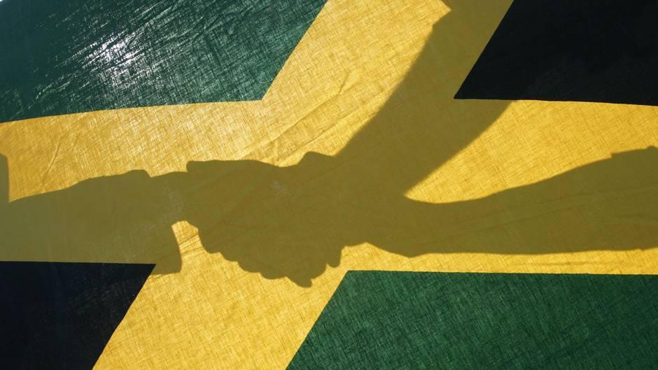 Händeschütteln - Schattenspiel unter einer Jamaika-Flagge