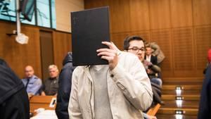 Ein Mann in heller Windjacke und grauem Pullover hält sich im Landgericht Frankfurt eine schwarze Mappe vor das Gesicht.
