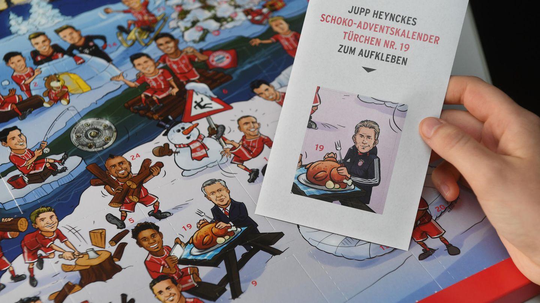 Eine Hand hält einen Aufkleber mit Jupp Heynckes vor einen Adventskalender von FC Bayern München