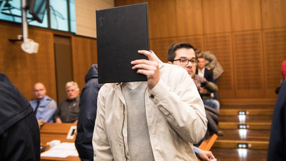 Prozessbeginn in Frankfurt: Der Angeklagte hält sich eine Mappe vors Gesicht
