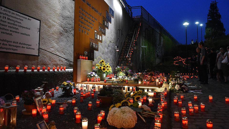 Menschen legen Blumen und Kerzen nieder an der Gedenkstätte zur Loveparade 2010 in Duisburg