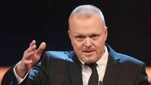 Ex-Entertainer Stefan Raab gestikuliert mit der rechten Hand. Er trägt einen schwarzen Anzug und eine schwarze Krawatte.