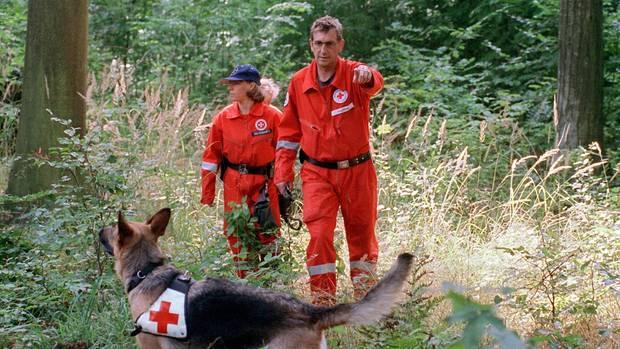 Ein Mann und eine Frau in orangenen Overalls folgen einem Suchhund durch einen Wald