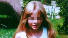 Johanna, ein achtjähriges, blondes Mädchen mit weißem Top und roter Hose steht auf einem Rasen mit Gänseblümchen