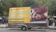 Ein Anhänger mit einem Werbeplakat für ein Sugardaddy-Datingportal steht in Paris am Straßenrand
