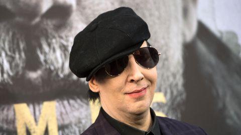 Mit Schiebermütze und Sonnenbrille lächelt Brian Warner alias Marilyn Manson in die Kamera