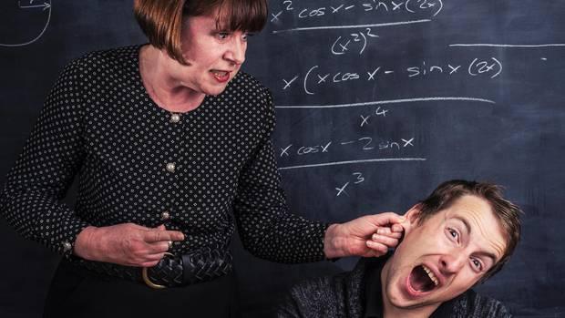 Ein Lehrer zieht einem Schüler die Ohren lang