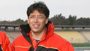 Stefan Kiefer, Chef des Motorrad-WM-Teams Kiefer Racing, steht in rot-schwarzer Jacke auf einer Rennstrecke