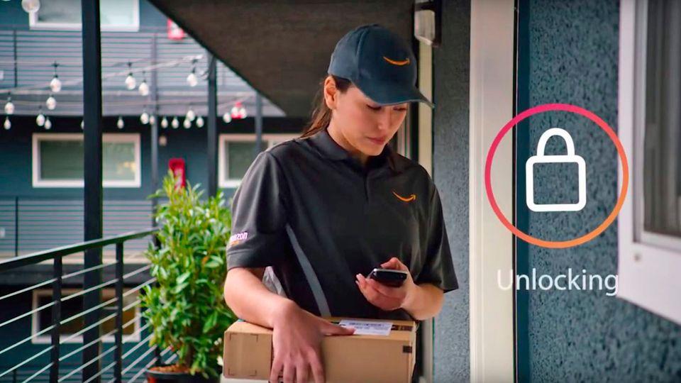 Eine Amazon-Mitarbeiterin öffnet mit ihrem Smartphone die Tür eines Kunden
