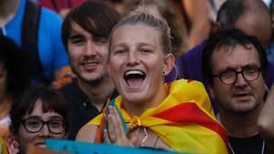 Eine blonde junge Demonstrantin mit katalanischer Flagge um die Schultern freut sich sichtlich über die Unabhängigkeit