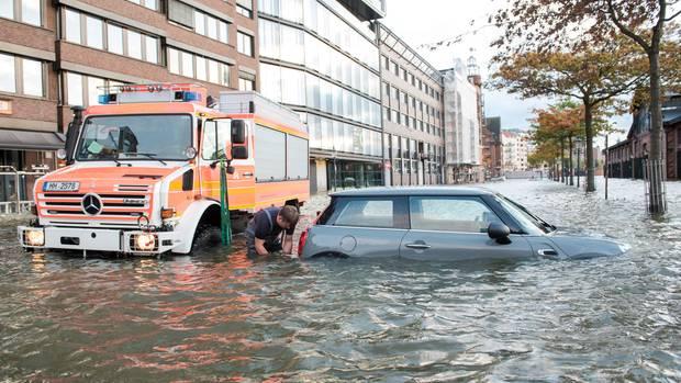 Am Hamburger Fischmarkt steht ein Auto im Wasser. Am Sonntagvormittags wurde es zwar sonnig in der Hansestadt, es gab aber eine Sturmflut.