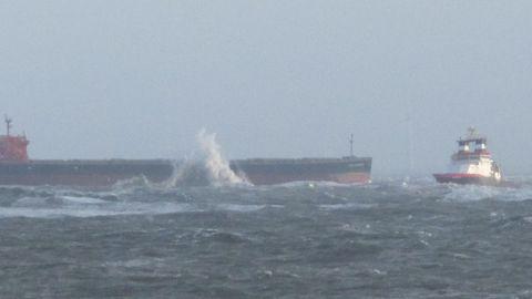 Mit einem Schlepper vor dem Bug liegt der Frachter Glory Amsterdam vor Langeoog auf Grund. An der Bordwand spritzt ein Brecher.