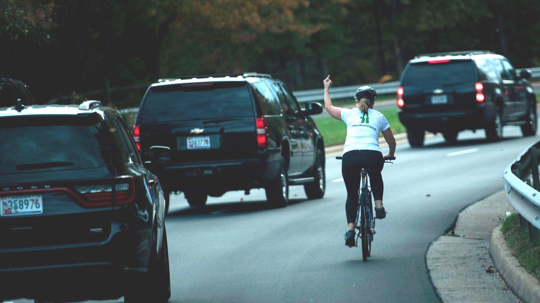 Eine Radfahrerin wird von Donald Trumps Auto-Konvoi überholt und zeigt einen Stinkefinger