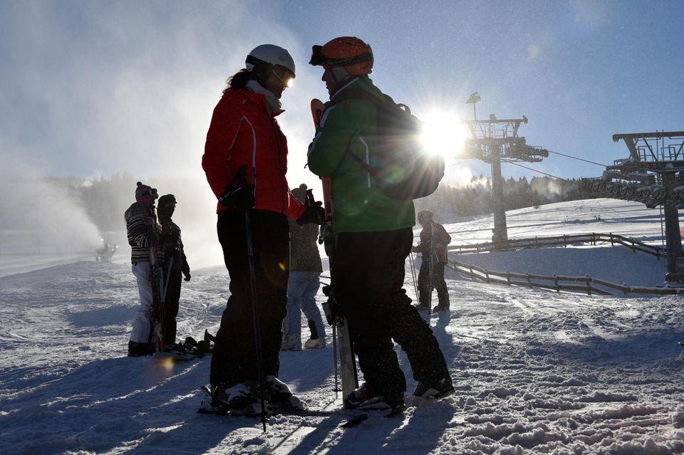 Auch ein Wintersportgebiet in Nordhessen: Skifahrer stehen im Gegenlicht an der Talstation in Willingen.