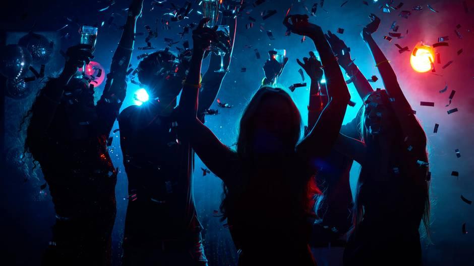Die Silhouetten tanzender Frauen setzen sich im Gegenlicht eines Nachtclubs ab