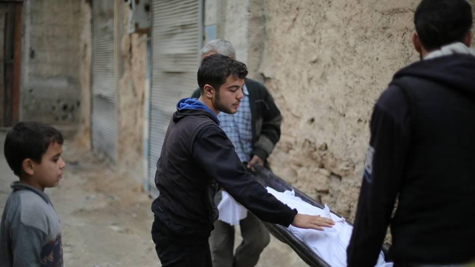 Ein Junge schaut zu, wie zwei Männer auf einer Bahre einen in ein Tuch gewickelten Kinderleichnam wegtragen.