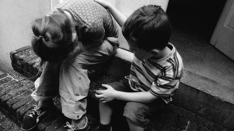 Unicef-Bericht zu sexueller Gewalt: Zwei Kinder sitzen auf einem Treppenabsatz vor einer Haustür