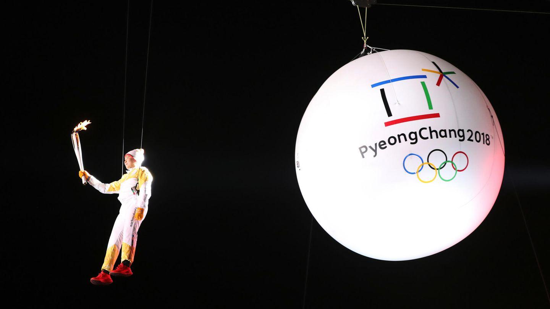 Der Südkoreaner Ryu Seung-min schwebt mit der olympischen Flamme in der Hand an einem Seil