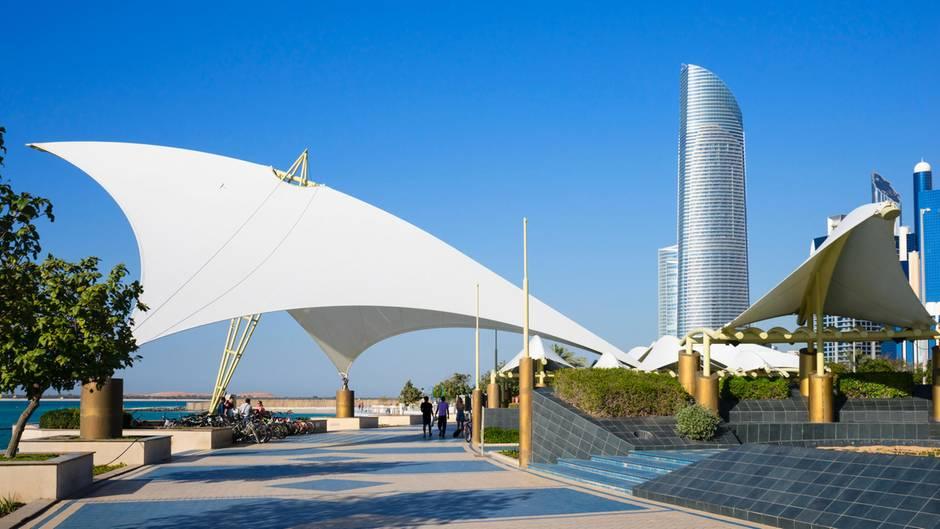 """Bummeln an der Corniche Abu Dhabi  Die Corniche erstreckt sich über viele Kilometer an der Küste entlang. Für viele ist die Strandpromenade eine Flaniermeile, andere bevorzugen den mit einer """"Blauen Flagge"""" ausgezeichneten Sandstrand zum Chillen - oder gehen zum Schwimmen und Abkühlen ins Wasser."""