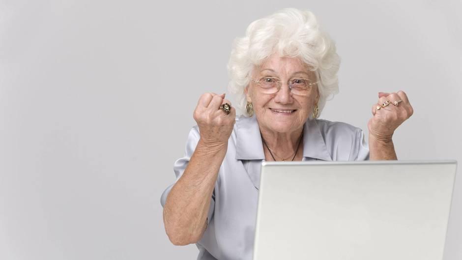 Eine Omi freut sich vor dem Computer über ihren Geburtstag