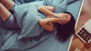 Eine Frau liegt angezogen im Bett und schlägt die Hände vors Gesicht