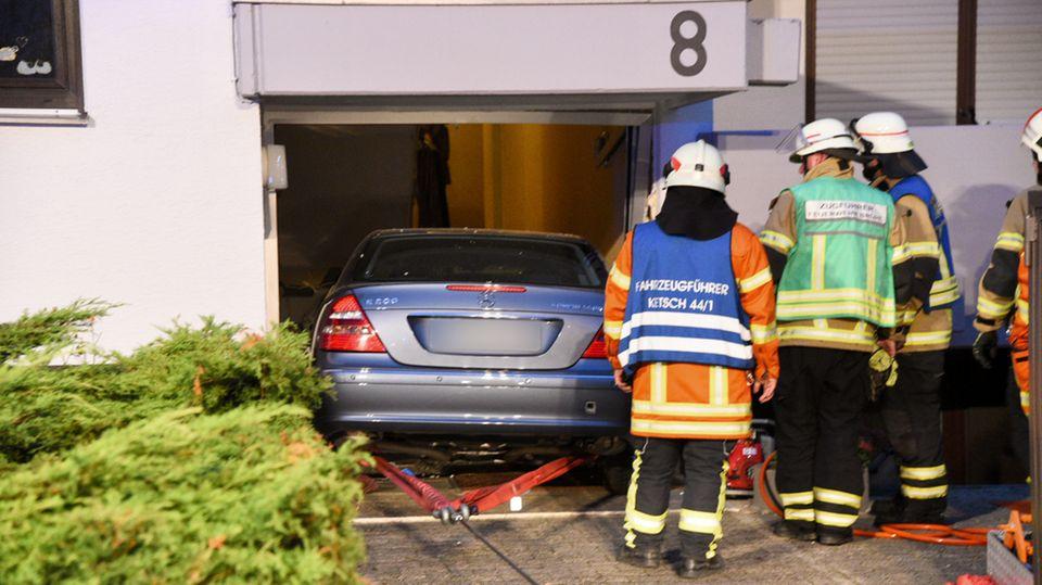 Drei Feuerwehrleute schauen zu, während ein Mercedes rückwärts aus einem demolierten Hauseingang gezogen wird