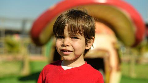 Eine Junge steht vor einem Schlumpfhaus in Form eines Fliegenpilzes