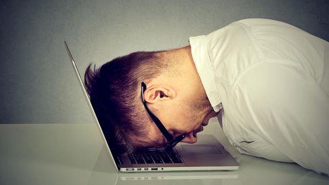Ein Mann legt verzweifelt seinen Kopf auf den Laptop