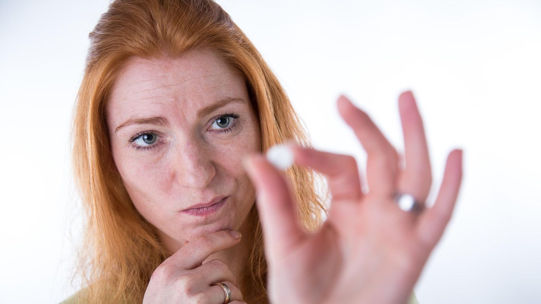 Eine Frau betrachtet skeptisch die Pille