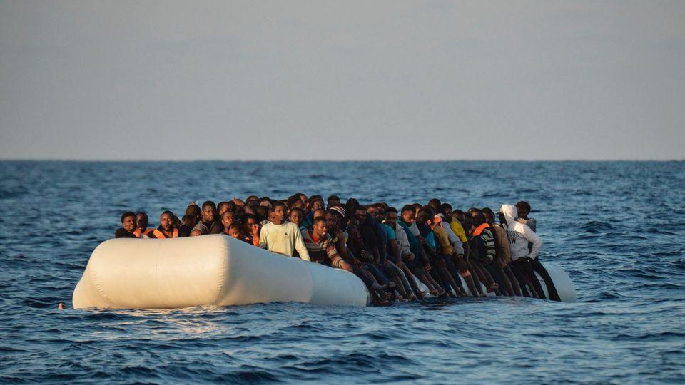 Ein großes Schlauchboot voller Flüchtlinge treibt auf dem Mittelmeer
