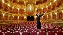 Mit ausgestreckten Armen und um schwarzen Kleid steht Anne-Sophie Mutter auf einem Sitz in einem reich verzierten Zuschauerraum