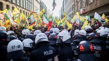 Polizisten blockieren in Düsseldorf eine Kurden-Demonstration, bei der verbotene Fahnen von Öcalan gezeigt werden