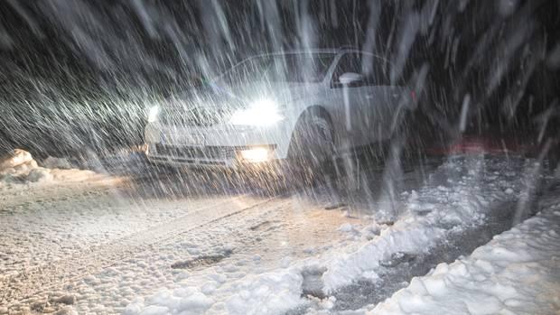 Schneetreiben in Bayern: Ein Auto auf der Passstraße bei Grasgehren