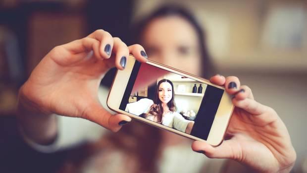 Eine Frau knipst mit der Kamera ihres Smartphones ein Selfie