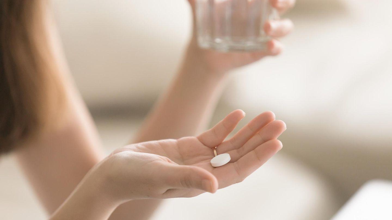 Eine junge Frau nimmt eine Tablette ein.