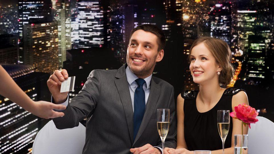 Ein Mann zahlt im Restaurant mit seiner Kreditkarte. Die Frau sitzt daneben und lächelt.