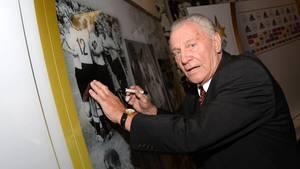 Hans Schäfer setzt sein Autogramm auf einem alten Foto der Fußball-Nationalmannschaft