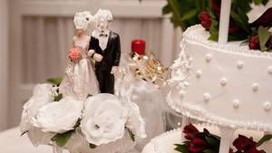 Auf einer Hochzeitstorte haben Braut und Bräutigam Sahne im Gesicht