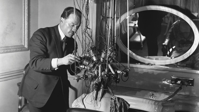 Sieht bedrohlicher aus als es ist: Ein Frisör verpasst einer Kundin eine Dauerwelle um 1921.