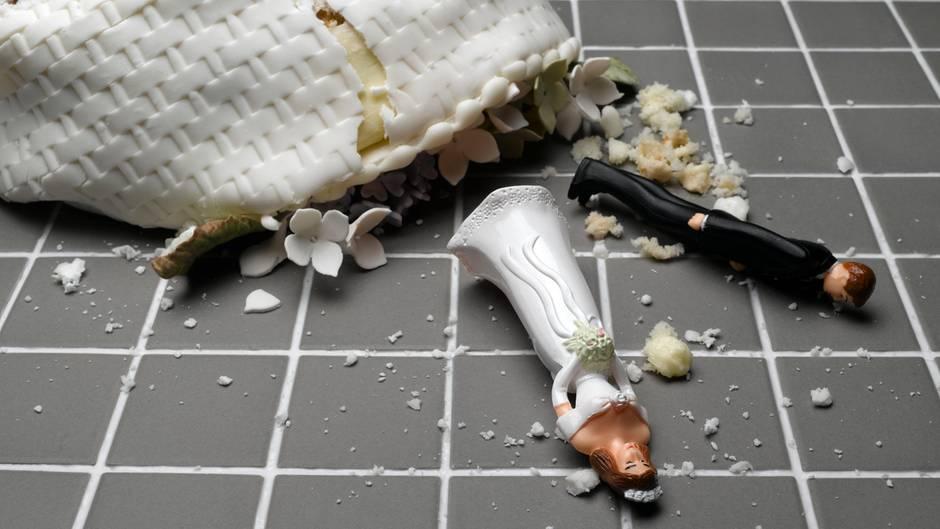 Eine Hochzeitstorte liegt zerstört auf deinem gekachelten Boden